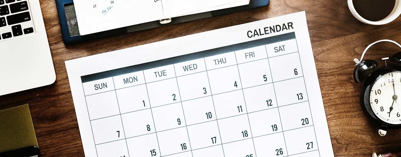 Kalender i nærheten av analog vekkeklokke