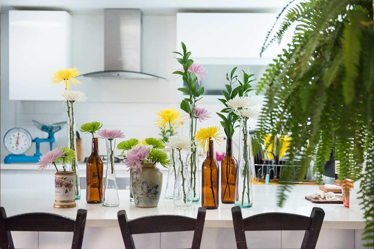 Bilde 11 - blomster i glassflasker på kjøkkenbenk