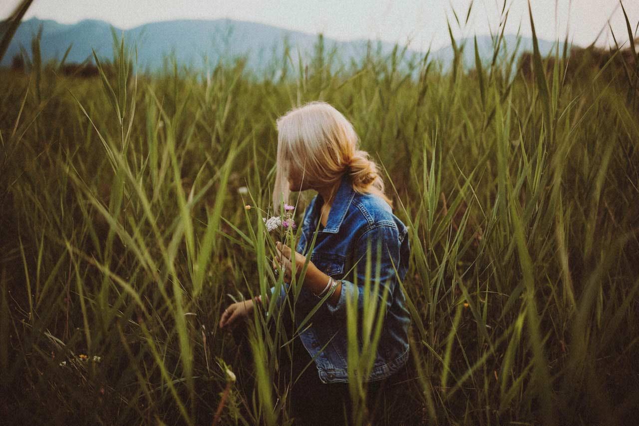 Bilde 12 - kvinne plukker blomster i høyt gress