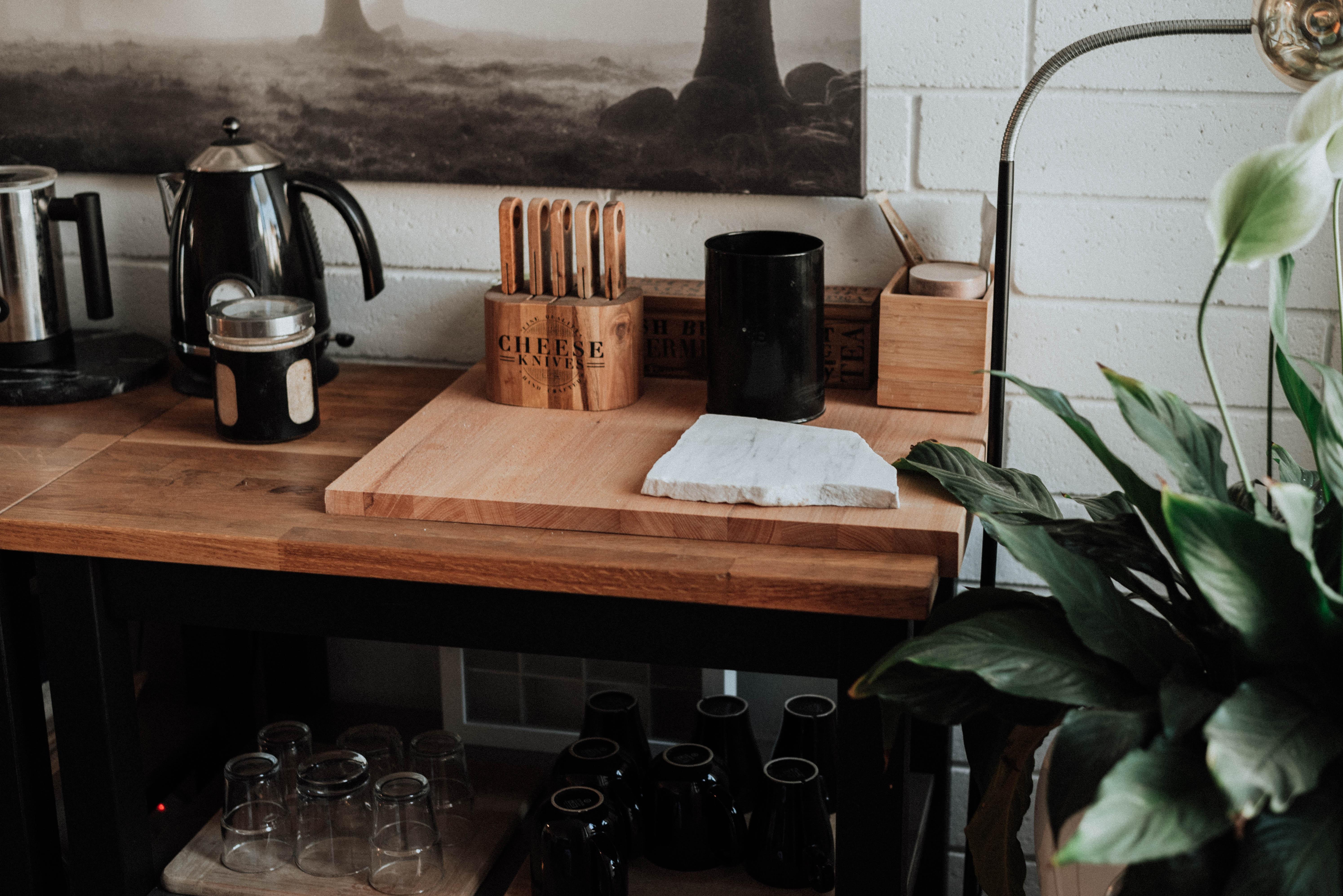 Ryddig kjøkkenbenk med tilbehør, vannkoker, briller og planter