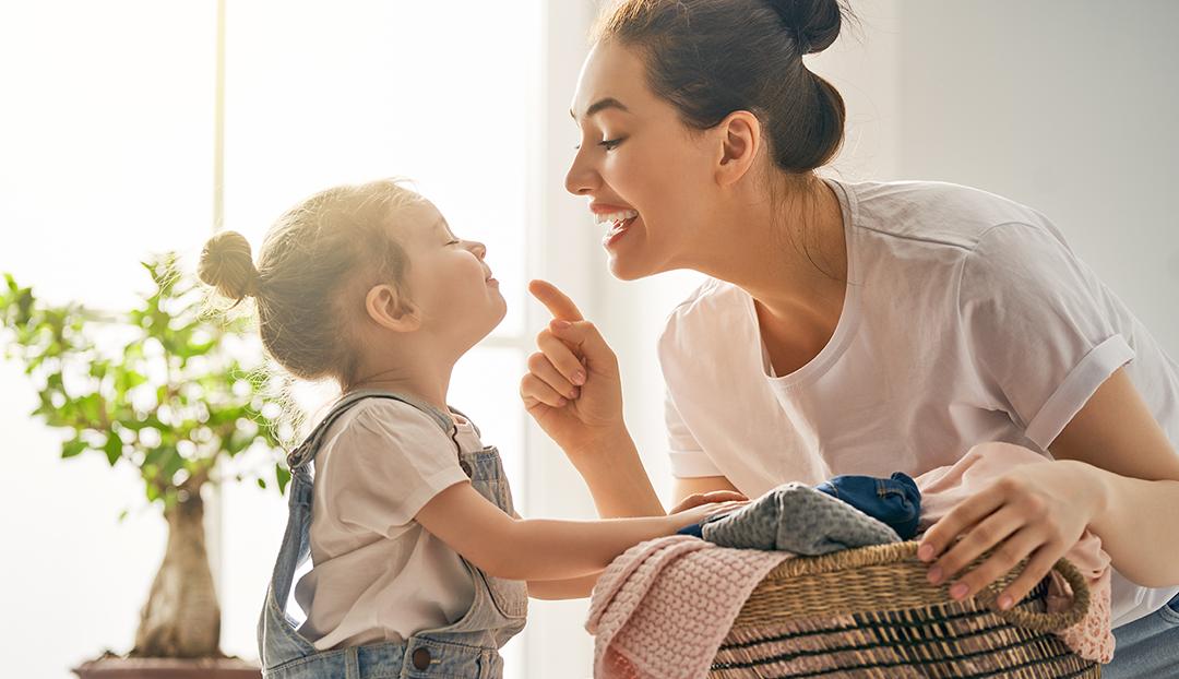 Mor og barn rydder og vasker sammen
